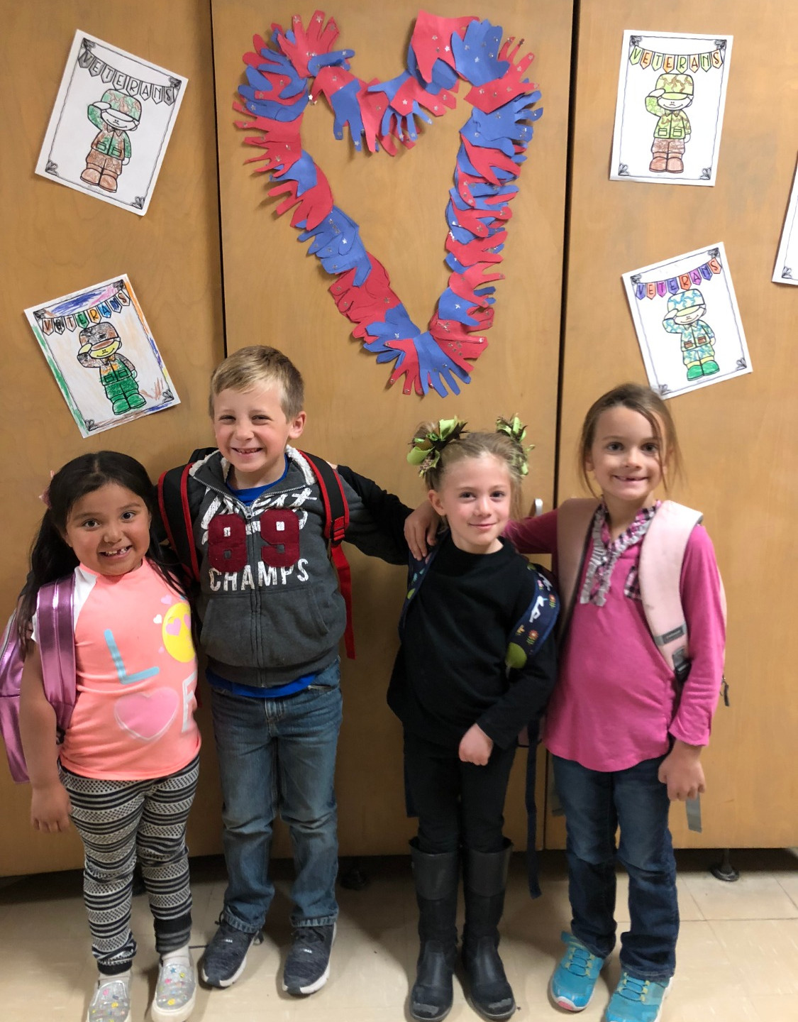 Students take a picture in front of their artwork for Veteran's Day.