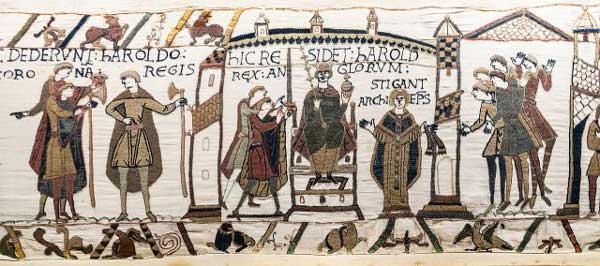 """König Harald II. auf dem Teppich von Bayeux. Die Beschriftung lautet: hIC RESIDET hAROLD, REX ANGLORVM – """"Hier sitzt Harald, König der Engländer""""; zu seiner Linken: STIGANT ARChIEP[iscopu]S –  """"Stigand, der Erzbischof"""""""