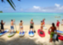 Group of people learn to stand up paddleboard on beach and lagoon in Rarotonga