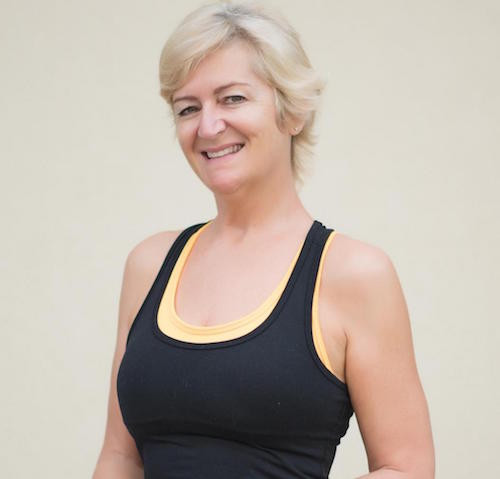 A head and shoulders shot of a smiling Julie Garrido is wearing yoga clothes.