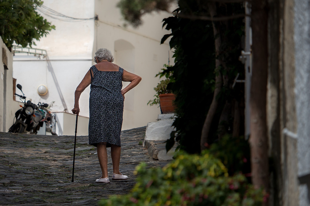 Julie Garrrido sees old lady walking outdoors with stick holding right hip which may be painful