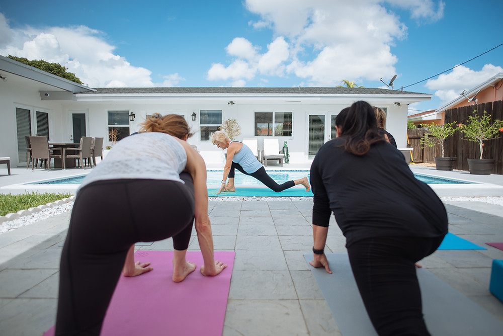 Julie Garrido is teaching a private Yin yoga lesson outside by swimming pool in Miami to two female students