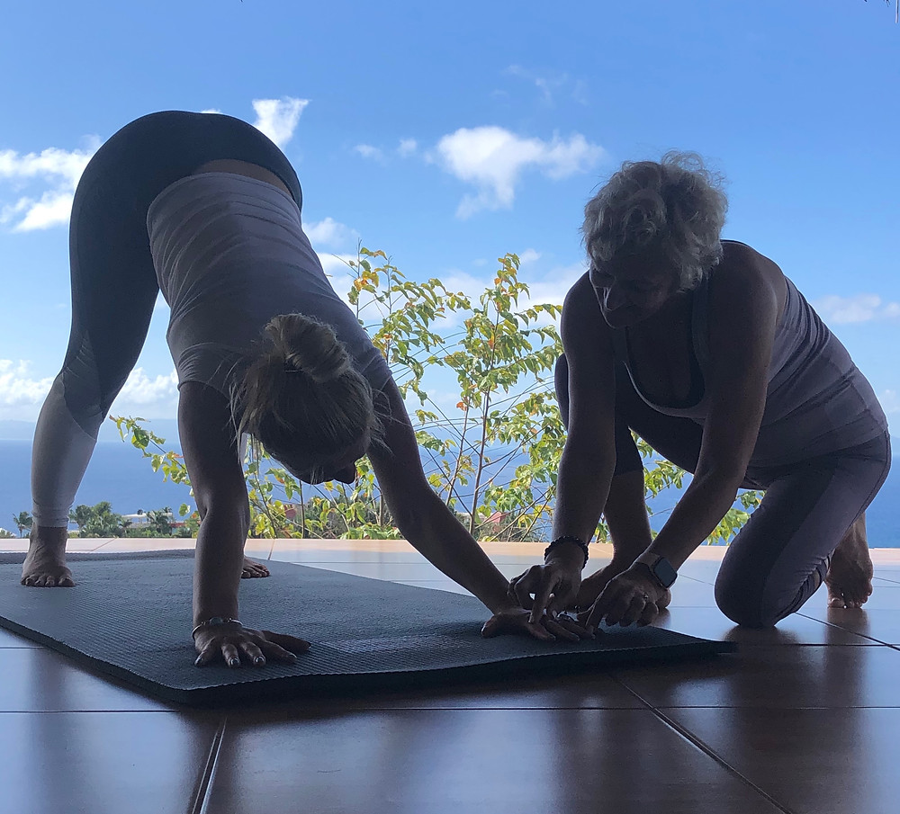 Julie Garrido is kneeling teaching a student in Downward Dog at a sunny Caribbean yoga retreat in the outdoors