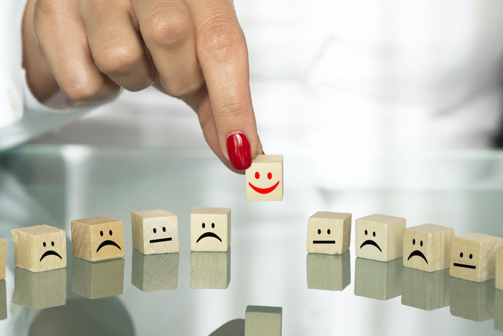 Woman adding a smiley face to a row of sad faces.