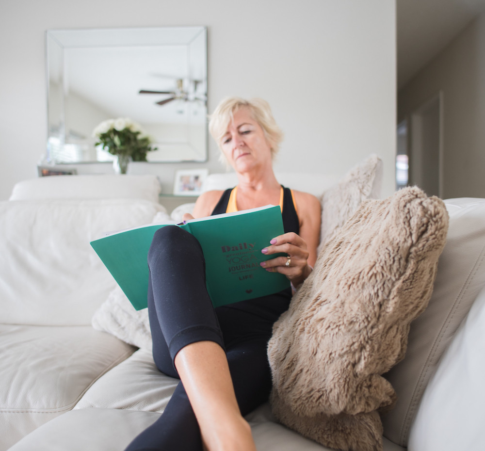 Julie Garrido is sitting comfortably on a couch wearing yoga gear and writing in a green yoga journal.