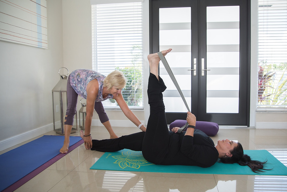 Julie Garrido is teaching private yoga to a lady in her home, She is lying down using a strap to assist her in a yoga pose.
