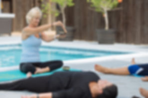 Julie Garrido using singing bowl at private group yoga class in Miami on her outdoor deck at home next to swimming poo