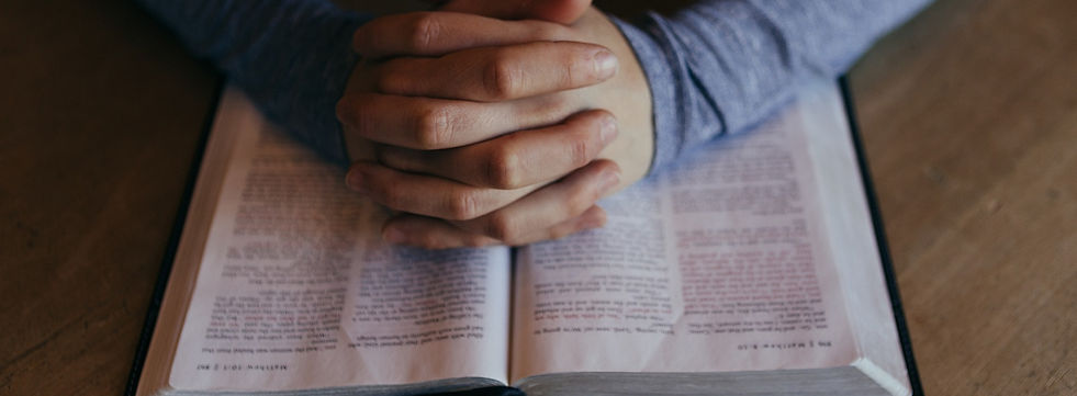 person praying at bible study