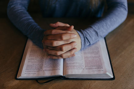 An open bible on a desk wit hands folded over