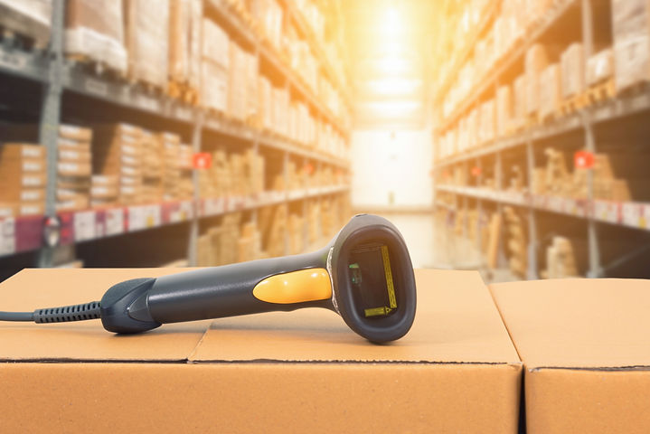 Barcode%20scanner%20in%20front%20of%20modern%20warehouse%20and%20scanning%20code%20on%20cardboard%20