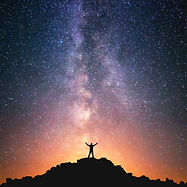 person standing on a hilltop reaching up to the starry sky