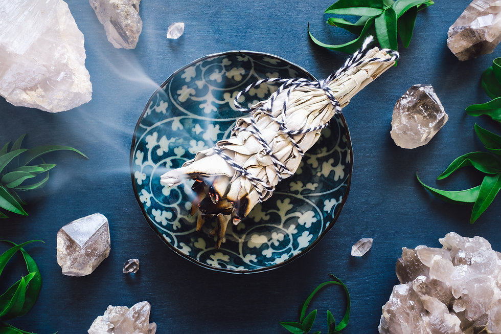 smudge stick smoldering in a ceramic bowl surrounded by crystals