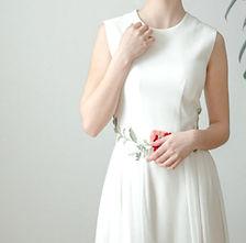Naisen päällä on silkkinen morsiuspuku, jonka vyötäröllä on kirjailtu kukka ja lehtiä.