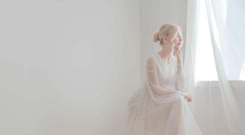 Nainen katsoo ikkunasta päällään valkoinen, pehmeästä tyllistä valmistettu ilmava mekko.