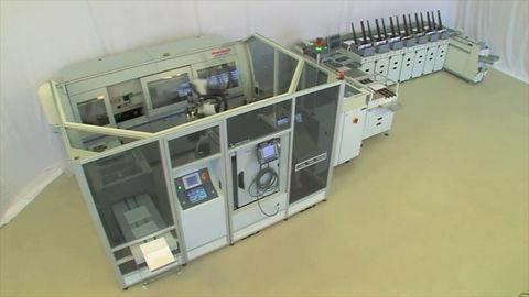 Roboterzelle zum automatischen Bestücken eines Standard-Klebebinders.