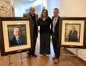 From left: Ed Tannenbaum, Carolyn Saligman and Eric Naftulin, bracketed by portraits of Ira Saligman (left) and Robert Saligman (right), dedicate a new wing of Robert Saligman Apartments in 2018. Courtesy of Carolyn Saligman