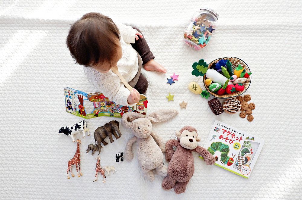 Toddler surrounded by toys.