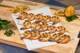 A mouth watering food photography capture of shrim skewers on a wooden cutting board.