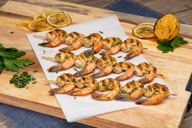 Succulent food photography of grilled shrimp skewers with parsley and lemon garnishes