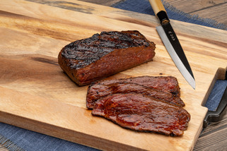A grilled rare steak lays sliced on a cutting board next to a high end steak knife