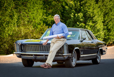 A golf course architect poses for a creative environmental portrait with his classic car.