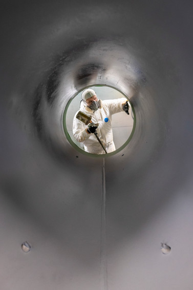 A creative portrait of a factory worker spray coating pipes in an industrial warehouse.