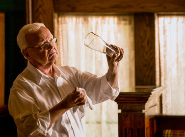 A distinguished older gentleman polishes up a craft beer glass in a beautiful naturally lit room.