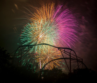 Vibrant fireworks light up the summer night sky, silhouetting the steel structure of a roller coaster at Busch Gardens Williamsburg in Virginia.