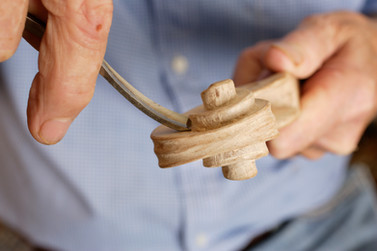 A detail image of an artisan handcrafting violins from wood.