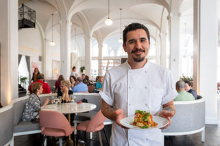 Environmental portrait of a chef holding a delectable entree inside of a bright and airy restaurant.