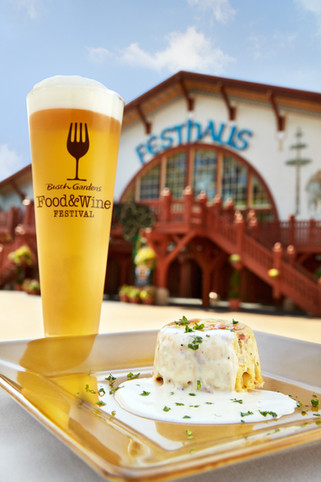 A frosty beer and savory tapas dish seen against the Festhaus as part of a culinary event at Busch Gardens Williamsburg in Virginia.