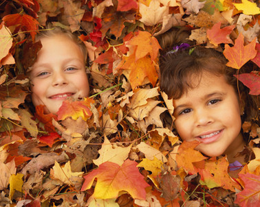 Children play in a pile of fall leaves as part of a travel and tourism advertising campaign.