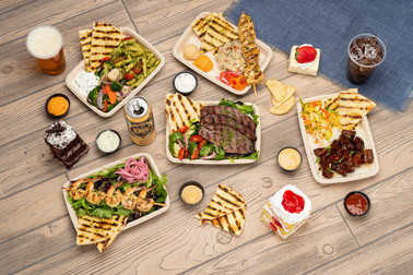 An overhead view of different health-conscious food offerings including grilled meats and greens laid out on a picnic table