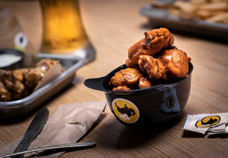 A gritty food photography shot of chicken wings amongst a table of beer and other sports bar foods at a Buffalo Wild Wings restaurant