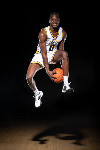 A dramatic action sports portrait of a Virginia Commonwealth University basketball player created on the court.