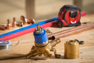 A tabletop product scene featuring parts for a residential plumbing installation