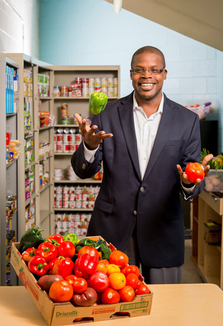 A well dressed man juggles fresh fruit and vegetables in a college's food pantry,
