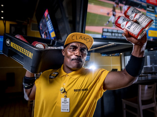 A dramatic portrait of a sports stadium beer vendor selling Budweiser inside a Buffalo Wild Wings restaurant