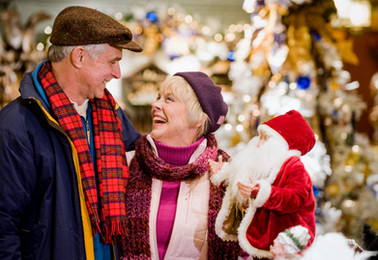 An advertising lifestyle image of a cozy older couple shopping for Christmas decorations.
