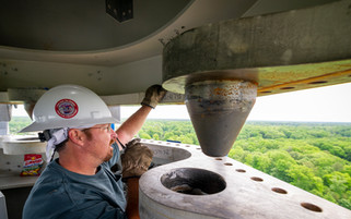 An industrial rigger guides two masts together from the inside while at elevation on a construction site.