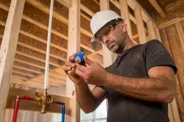 A location style product picture of a plumber installing a valve in new residential construction