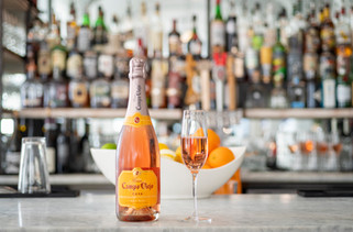 A rosy glass of sparkling wine sits atop a white stone bar top with shelves of drinks in the background