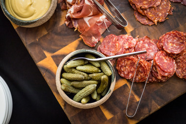 An overhead view of a scrumptious food photography spread of a charcuterie board featuring prosciutto and gherkins