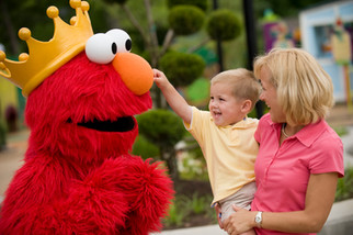 A mother holds her cheerful son as he gets an up close and personal meeting with Elmo for a commercial photoshoot at a theme park.