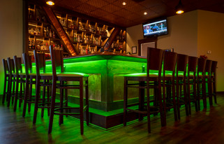 A neatly staged bar area in a restaurant featuring the colored LED under-lighting