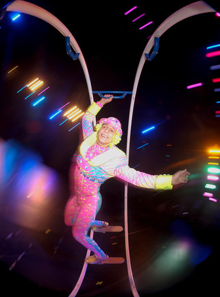 A colorfully dressed performer warms up in a giant rolling ring for an elaborate circus style themed production in Virginia.