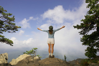 A recreational lifestyle advertisement of a woman enjoying the view of the blue skies atop a mountain in Virginia.