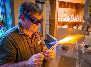 An artisan shapes glass in a craft workshop at a theme park in Williamsburg, Virginia