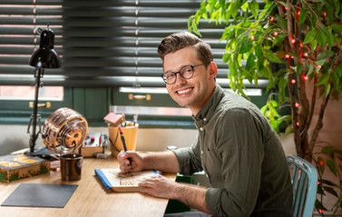 A young entrepreneur poses for a corporate environmental portrait at the desk of his start-up company.