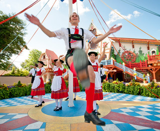 A Bavarian themed maypole dance, complete with lederhosen and dirndl outfits, is seen against a bright blue sky in the German area of Busch Gardens in Virginia